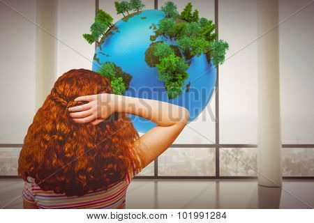 Brunette girl with hand behind head against earth floating in room