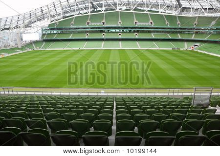 Rows of green seats in an empty stadium. Focus on front seats