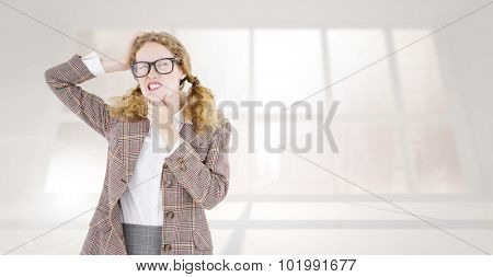 Geeky hipster thinking with hands on chin and temple against bright white room with windows
