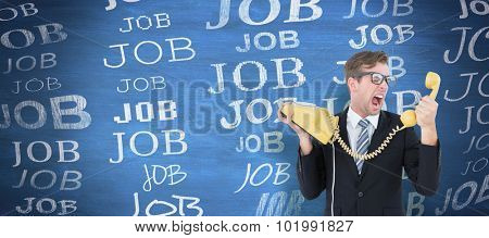 Geeky businessman shouting at telephone against blue chalkboard
