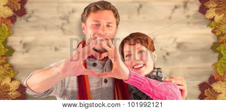 Couple making a heart shape against bleached wooden planks background