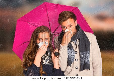 Couple blowing nose while holding umbrella against country scene