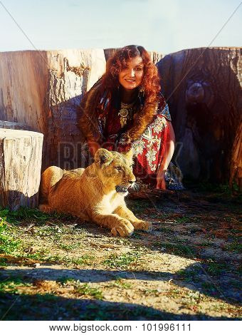 young woman with ornamental dress and gold jewel playing with lion cub in nature.