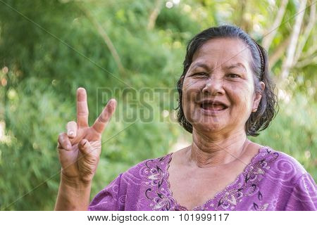 Old Thai Woman Smiling And Showing V Sign