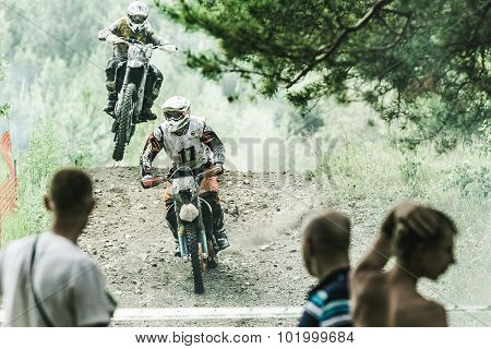Motocross driver on wet and muddy terrain from the mountain