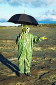 image of scoria  - Man in suit and gas mask with umbrella waiting for acid rain - JPG