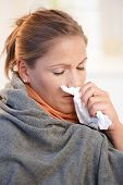 foto of blowing nose  - Young woman caught cold feeling bad blowing her nose wrapped up in blanket - JPG