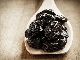 picture of prunes  - Healthy food good cuisine. Closeup dried plums prunes fruits on wooden spoon rustic table background ** Note: Shallow depth of field - JPG