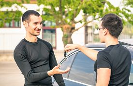 pic of going out business sale  - Happy satisfied young man receiving car keys after second hand sale  - JPG