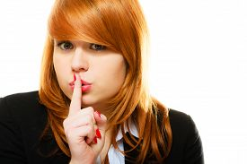 pic of hush  - Business woman redhaired girl asking for silence or secrecy with finger on lips hush hand gesture - JPG