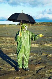 stock photo of scoria  - Man in suit and gas mask with umbrella waiting for acid rain - JPG