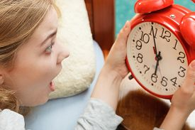 stock photo of panic  - Panic woman waking up late in morning turning off alarm clock - JPG