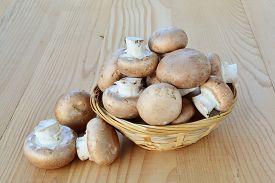 picture of crimini mushroom  - Cremini mushrooms brown cap in a basket over wooden table - JPG