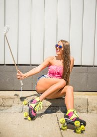 stock photo of roller-derby  - Smiling young woman in rollers is making selfie photo with selfie stick - JPG