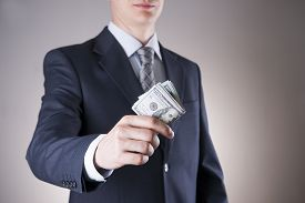 pic of corruption  - Businessman with money in studio on a gray background - JPG