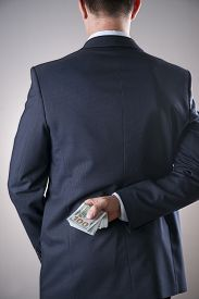 foto of corruption  - Businessman with money in studio on a gray background - JPG