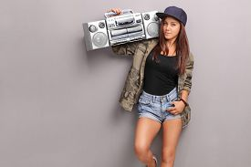 stock photo of rap-girl  - Teenage girl in hip hop clothes holding a ghetto blaster over her shoulder and looking at the camera - JPG