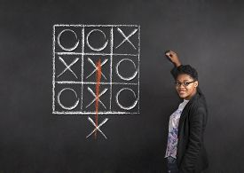 pic of tic  - South African or African American woman teacher writing tic tac toe on chalk black board background - JPG
