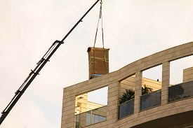 stock photo of boom-truck  - Delivery of the refrigerator in  original packaging to the penthouse via truck crane - JPG