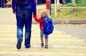 stock photo of daycare  - father walking little daughter with backpack to school or daycare - JPG