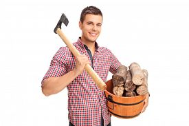 stock photo of shoulder-blade  - Young man carrying an axe over his shoulder and holding a bucket full of logs isolated on white background - JPG