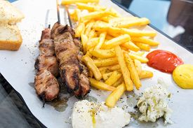 stock photo of souvlaki  - Souvlaki portion with french fries served on a table in a restaurant - JPG