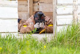 pic of paintball  - Paintball player lying in ambush aiming outdoors - JPG