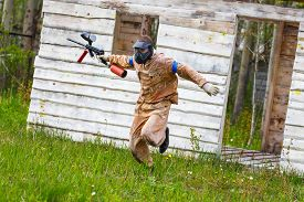 foto of paintball  - Dynamic paintball sportsman on the run outdoors - JPG