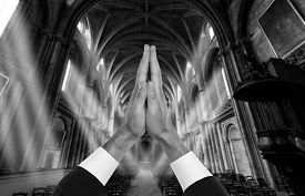 image of priest  - Priest hands inside a church with sun rays - JPG
