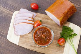 stock photo of smoked ham  - Homemade tomato sauce in glass jar with tasty ham smoked whole and sliced close - JPG