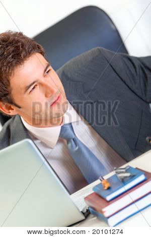 Alert modern business man sitting at office desk and looking in corner. Close-up