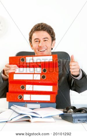 Sitting at office desk smiling businessman looking out from pile of folders and showing thumbs up