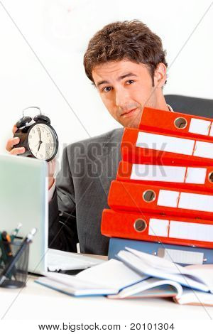 Dissatisfied modern businessman sitting at office desk with pile of folders and holding alarm clock
