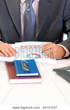 Businessman sitting at office desk and working with documents. Closeup.