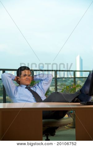 Reclined Hispanic Businessman Hand Behind Head