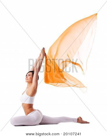 Young woman in yoga pose and flying fabric