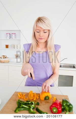 Beautiful Blonde Female Cutting Peppers In Modern Kitchen Interior