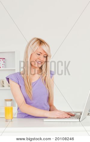 Beautiful Woman Relaxing On A Laptop In The Kitchen
