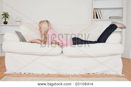 Young Smiling Woman Relaxing With A Laptop While Lying On A Sofa