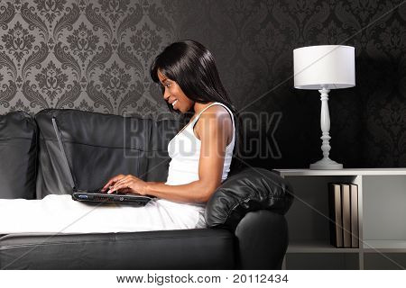 Beautiful Black Woman At Home Using Laptop