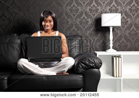 Happy Smiling Black Woman On Sofa Surfing Internet