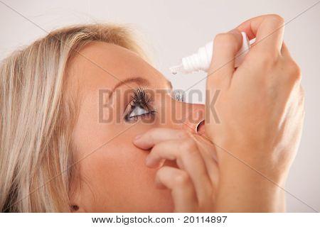 Ojo de la mujer y el cuentagotas con gotas de agua en Punta