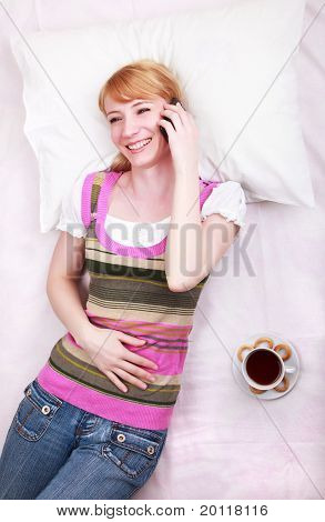 Woman Lying In Bed And Talking On Her Mobile