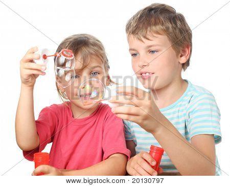 menino e menina sentada, sorrindo e soprando bolhas isolaram no branco