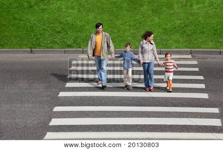 mother and father holds hand of little daughter and son and crossing road, green fence and grass