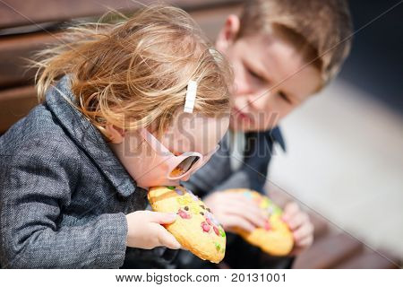 Portrait of two kids eating big cookies