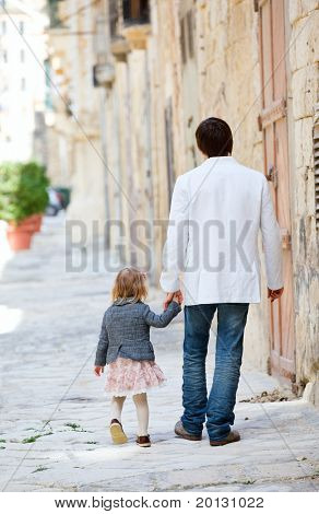 Father and his little daughter outdoors in city on sunny spring day
