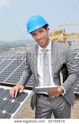 Businessman standing on solar panel installation