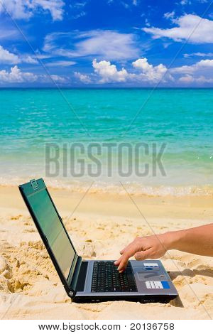 Computer And Hand On Beach