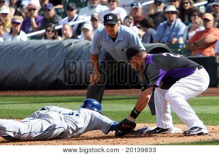 SCOTTSDALE, AZ - MARCH 7: Los Angeles Dodgers outfielder Tony Gwynn Jr avoids a tag by Colorado Rockies infielder Ty Wigginton at Salt River Fields at Talking Stick on March 7, 2011 in Scottsdale, AZ.